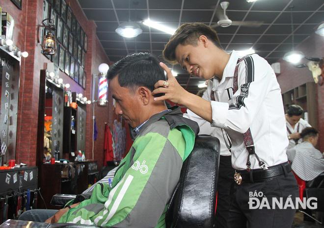 Chủ tiệm Nguyễn Minh Vương (phải) đang cắt tóc cho một tài xế xe ôm công nghệ.